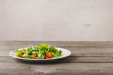 Plate of fresh salad on wooden table with free place on the table on a light background Stock Photo