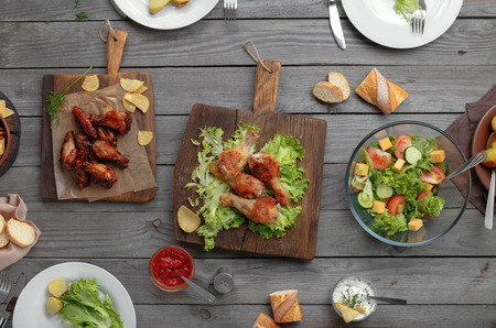 view to outside: Outdoors Food Concept. On the wooden table different food, grilled chicken legs, buffalo wings, bread, salad, potatoes, top view
