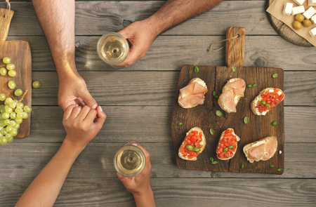 tenderly: Man tenderly holds his girlfriends hand. Couple drinking wine with snacks for wine, top view Stock Photo
