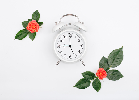Alarm clock with small pink roses on rose leaves on white background. Flat lay. Top view