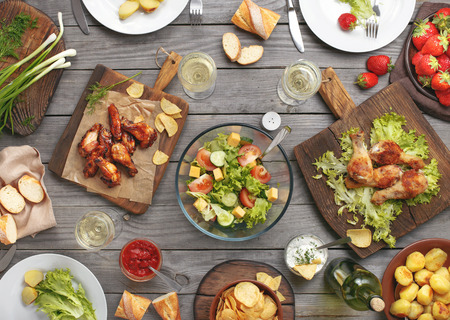 Different food cooked on the grill on a wooden table, grilled chicken legs, buffalo wings, salad, potatoes, bottle of wine and three glasses of wine and strawberry.