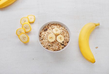 Healthy breakfast with muesli and banana, top view