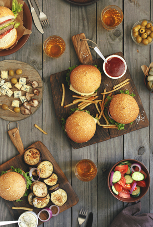 Different food on a wooden table, burgers, fries, grilled eggplant, salad, shiitake mushrooms, pickles, sauces, roquefort cheese, olives and light beer, top view.