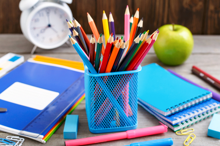 Colour pencils and school supplies close up on wooden desk Stock Photo