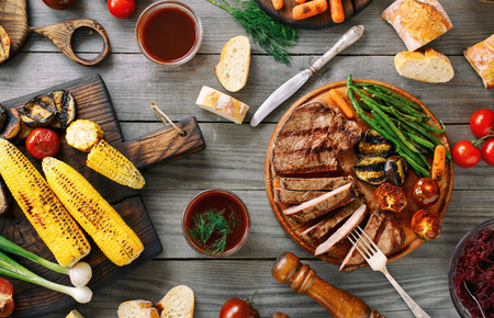 Juicy sliced grilled beef steak with various grilled vegetables on wooden table. Top view. Foto de archivo