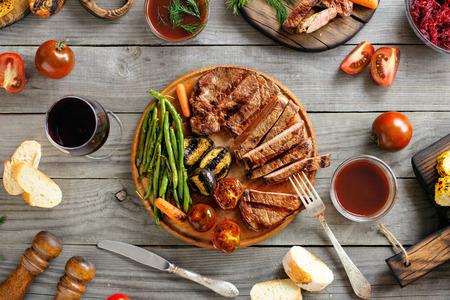 焼肉ステーキ vaus グリル野菜と木製のテーブルの上にワインのガラス。トップ ビュー 写真素材