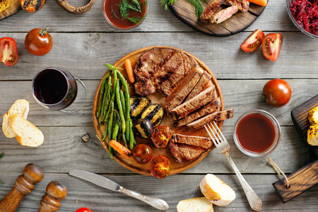 Grilled beef steak with various grilled vegetables and glass of wine on wooden table. Top view Stockfoto