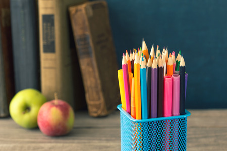 Set of colored pencils on a background of the books. School background
