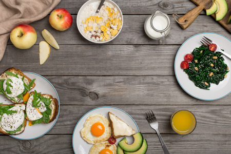 plates of food: Frame of fried egg, poached eggs, cheese sandwiches, avocado, apple, spinach salad, muesli, milk and orange juice on a wooden table, overhead view Stock Photo