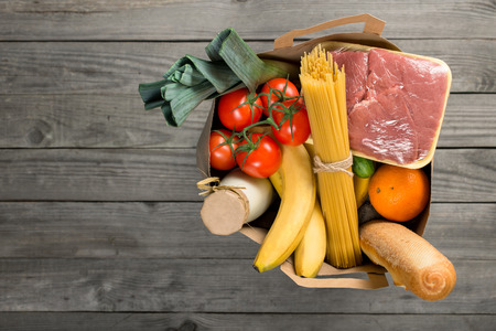 Full paper bag of groceries on wooden background with copy space, top view