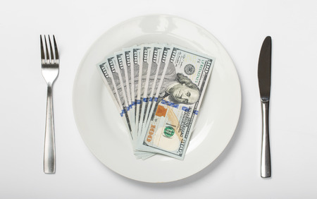 onehundred: Money on a white plate on a white background, top view