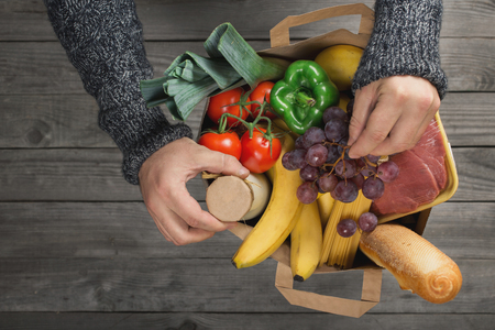 Man holding bag full of different healthy food on wooden table, top view