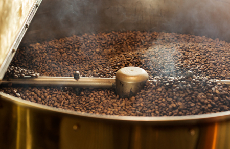 Freshly baked aromatic and dark coffee beans in professional roasting machine