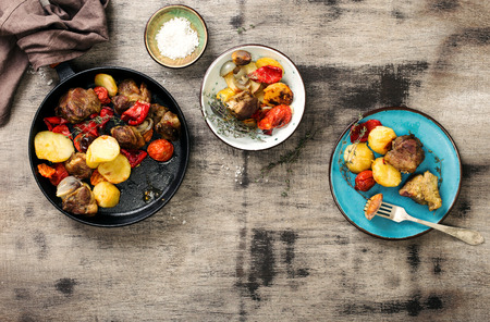 Wooden dining table with fried meat with vegetables in a frying pan and plates with food, top view Foto de archivo