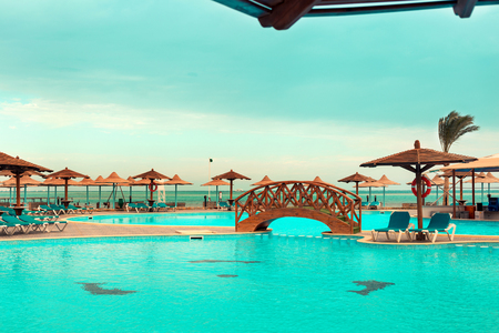 Swimming pool with sunbeds and umbrellas on the coast, Egypt Stock Photo
