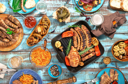 Variety of food grilled on wooden table, top view. Outdoors food Concept Foto de archivo