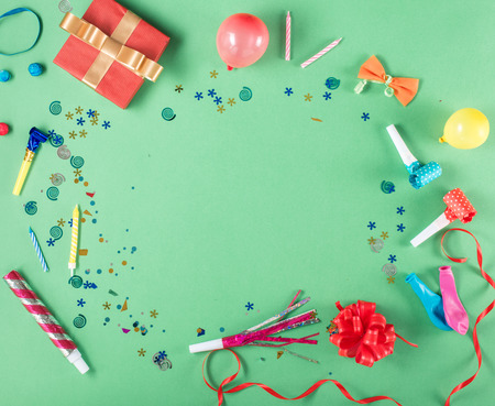 Colorful party frame with red gift box with various party confetti, balloons, streamers, noisemakers and decoration on a green background. Colorful celebration background. Flat lay.