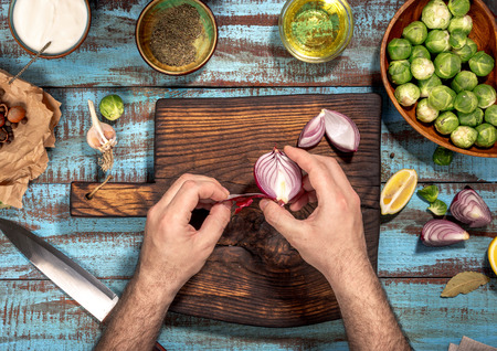 Man cooking a healthy food of brussels sprouts on a blue wooden table. Ingredients for healthy food, top view. Rustic style