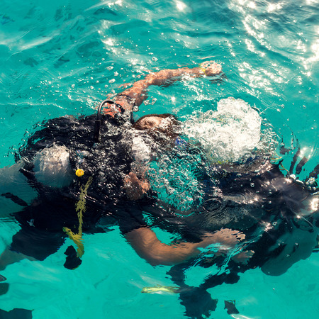 Couple divers plunged into the ocean on a sunny day, top view