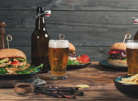 別のハンバーガー、スナック、木製のテーブルにラガービールをクローズ アップ