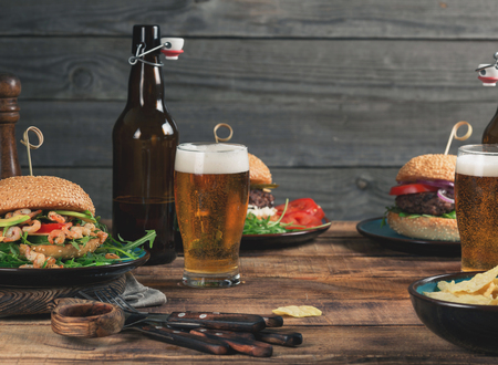 Different burgers, snack and lager beer on a wooden table close up