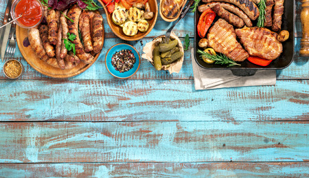 Variety of grilled food on the blue wooden table on a sunny day, grilled steak, grilled sausage and grilled vegetables. Top view. Outdoors Food Concept