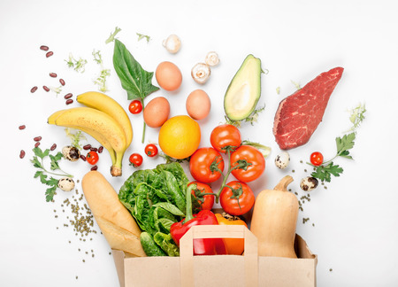 Bolsa de papel completo de diferentes alimentos saludables sobre un fondo blanco. Vista superior. Tumbado Foto de archivo - 73010693