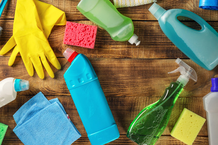 Cleaning supplies on wooden table with copy space, top view Foto de archivo