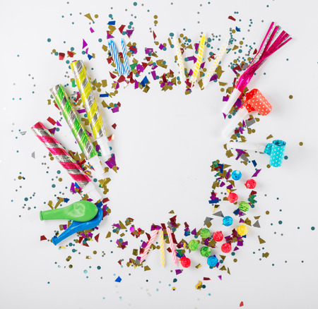 Frame with confetti, balloons, streamers, noisemakers and decoration on white background. Colorful celebration background. Top view. Flat lay