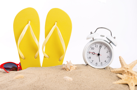 woman sandals: Yellow beach slippers with white vintage alarm clock, sunglasses and seashells in the sand on a white background. Summer background Stock Photo
