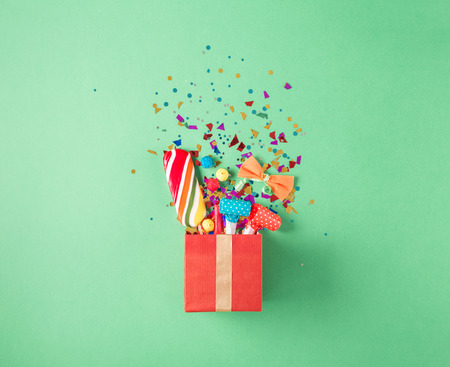 Red gift box with various party confetti, balloons, streamers, noisemakers and decoration on a green background. Flat lay