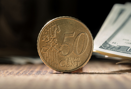 Fifty euro cents close up on wooden table on black background