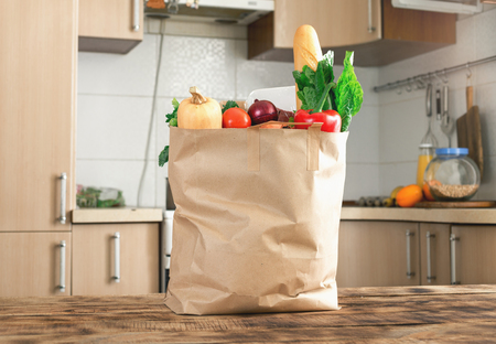 Paper bag full of healthy food on a wooden table in the kitchen
