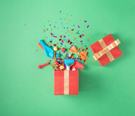 serpentinas: Caja de regalo roja con diversos confeti, globos, serpentinas, noisemakers y decoración del partido en un fondo verde. Fondo colorido de la celebración. Endecha plana. Foto de archivo