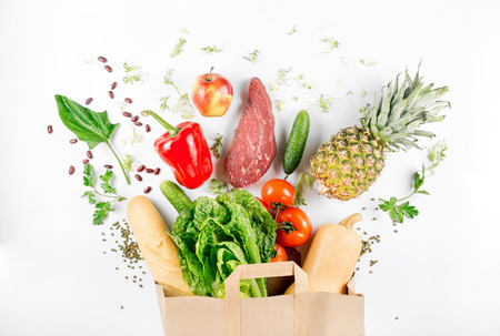 Paper bag full of healthy food on a white background. Top view. Flat lay