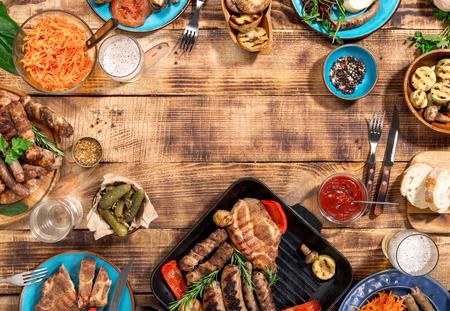 Bifteck, saucisses et légumes grillés appétissants sur une table de pique-nique en bois avec copie, vue de dessus