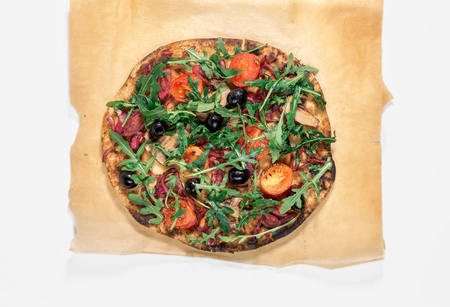 Vegetarian pizza with marinated red onions, mushrooms, tomatoes, olives and arugula on white background, top view. Delicious and healthy food
