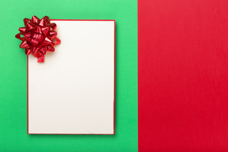 celebratory event: Blank card with a red bow on a colorful background, top view. Colorful celebration background