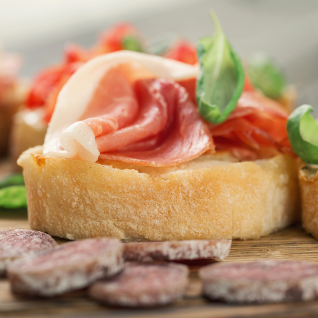 Bruschetta with prosciutto and basil on a wooden table close up Stock Photo