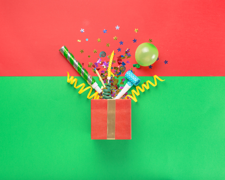 Red gift box with various party confetti, balloons, streamers, noisemakers and decoration on a multicolored background. Colorful celebration background. Flat lay