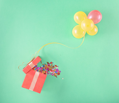 Red gift box with and set of balloons on a light background. Colorful celebration background. Flat lay