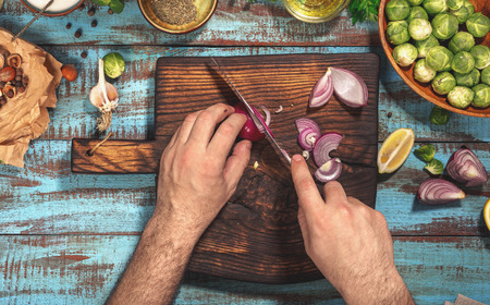 Man preparing healthy food on kitchen wooden table, top view Stock Photo