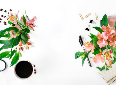 Female workspace with different office accessories, cup of coffee and bouquet of flowers with copy space. Flat lay, top view