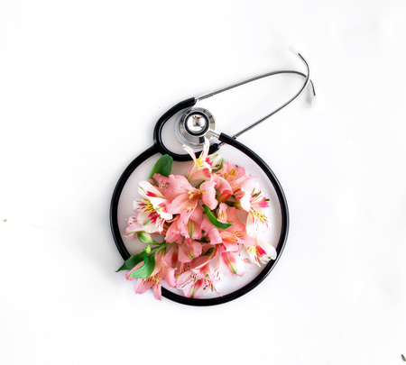 Stethoscope with alstroemeria on white background. Flat lay, top view