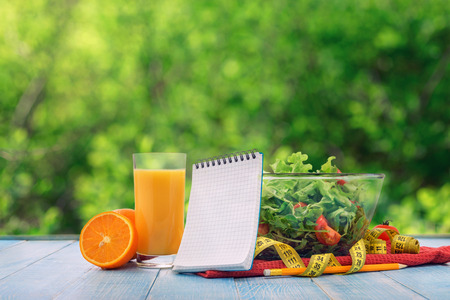 yellow notepad: Empty notebook with set of healthy diet food on a wooden table against the background blur green leaves bokeh. Fresh salad, glass of orange juice and a measuring tape with a empty notebook. Concept of a healthy food
