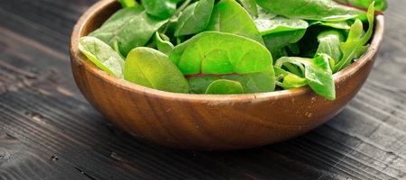 Wooden plate with mix of leaf salad close up. Healthy food. Green meal Stock Photo