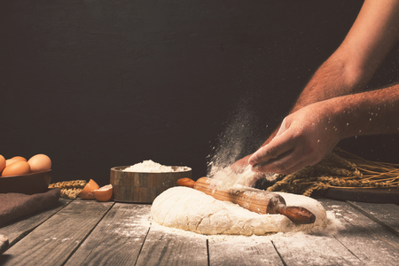 Men hands sprinkle a dough with flour close up. Man preparing bread dough Imagens