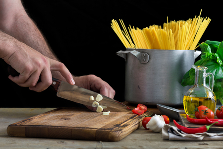 Man ?ooking an Italian pasta on a light wooden table
