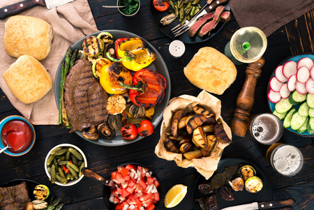 snacking: Meat and vegetables cooked on a grill on a dark wooden table with wine and beer, top view. Dinner table concept