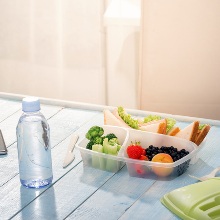 Healthy lunch box with sandwich, fresh vegetables, fruits and bottle of water on blue wooden table Stock Photo
